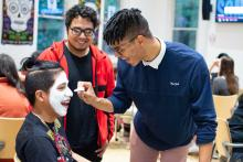 Smiling students paint one another's faces in Day of the Dead style