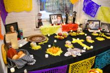 The offrenda, an offering table featuring yellow flower petals, small clementines / oranges, and framed photos of loved ones who have passed on.